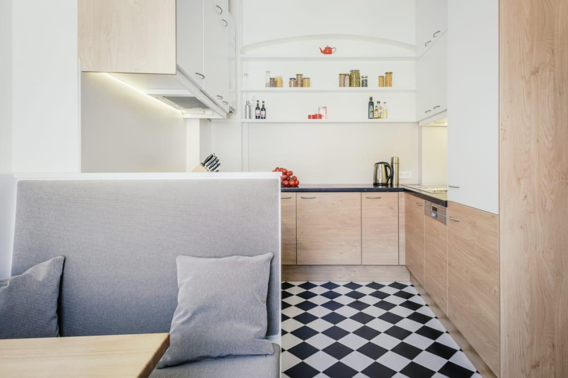 "<p>A minimalist interior style was set up in this old flat. With a checkerboard pattern stretching across the floor, a pleasant bit of contrast is achieved that makes the rest of the room's subtle style seem more elegant. </p><p>The round arch in the background might have been a doorway once upon a time, but now it's been filled up and transformed into a stylish niche for storage- and display purposes. The original floor plan was elegantly integrated into the contemporary ambience of the <a rel=""nofollow"" href=""https://www.homify.co.uk/rooms/kitchen"">kitchen</a>.</p>  Credits: homify / raumdeuter GbR"