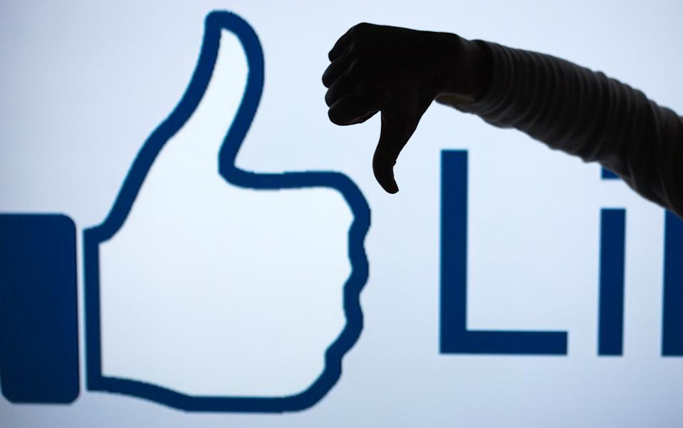 ILLUSTRATION - A woman makes the 'thumbs down' sign with her fist and thumb in front of an enlarged 'Like' symbol of the social netweorking site Facebook in Schwerin, Germany, 04 April 2013 (STAGED PICTURE). The social network counts more than 25 million users in Germany alone, but it keeps losing more and more especially young users to other online services. Photo:Jens Buettner | usage worldwide   (Photo by Jens Büttner/picture alliance via Getty Images)