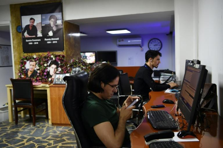 In the Tolo News office in Kabul, reporters work beside photo tributes to two colleagues killed in a suicide attack in September