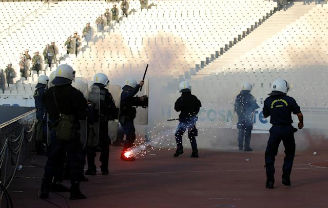 Soccer Football - Greek Cup Final - AEK Athens vs PAOK Salonika - Athens Olympic Stadium, Athens, Greece - May 12, 2018 Police look on as a flare goes past before the match REUTERS/Alkis Konstantinidis