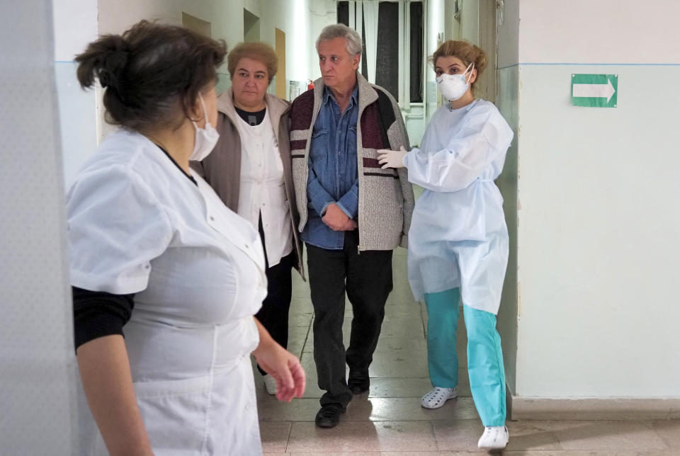 Medical personnel accompany a coronavirus patient in an infectious diseases clinic in Stepanakert, the separatist region of Nagorno-Karabakh, Tuesday, Oct. 20, 2020. Nagorno-Karabakh, which lies within Azerbaijan but has been under the control of ethnic Armenian forces since a war there ended in 1994, faces an outbreak of the coronavirus amid the largest outbreak of hostilities in more than a quarter-century. (AP Photo)