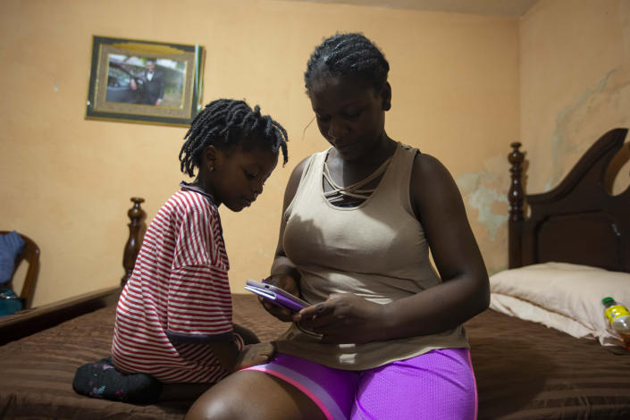 Deported from the United States a day before, Delta de Leon and her 2-year-old daughter Chloe, look at pictures from their time in Chile, in their temporary bedroom, at a relative's home in Port-au-Prince, Haiti, Thursday, Sept. 23, 2021. Chole was born in Chile. (AP Photo/Joseph Odelyn)