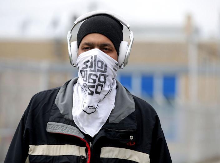 A man using a bandana to cover his face.