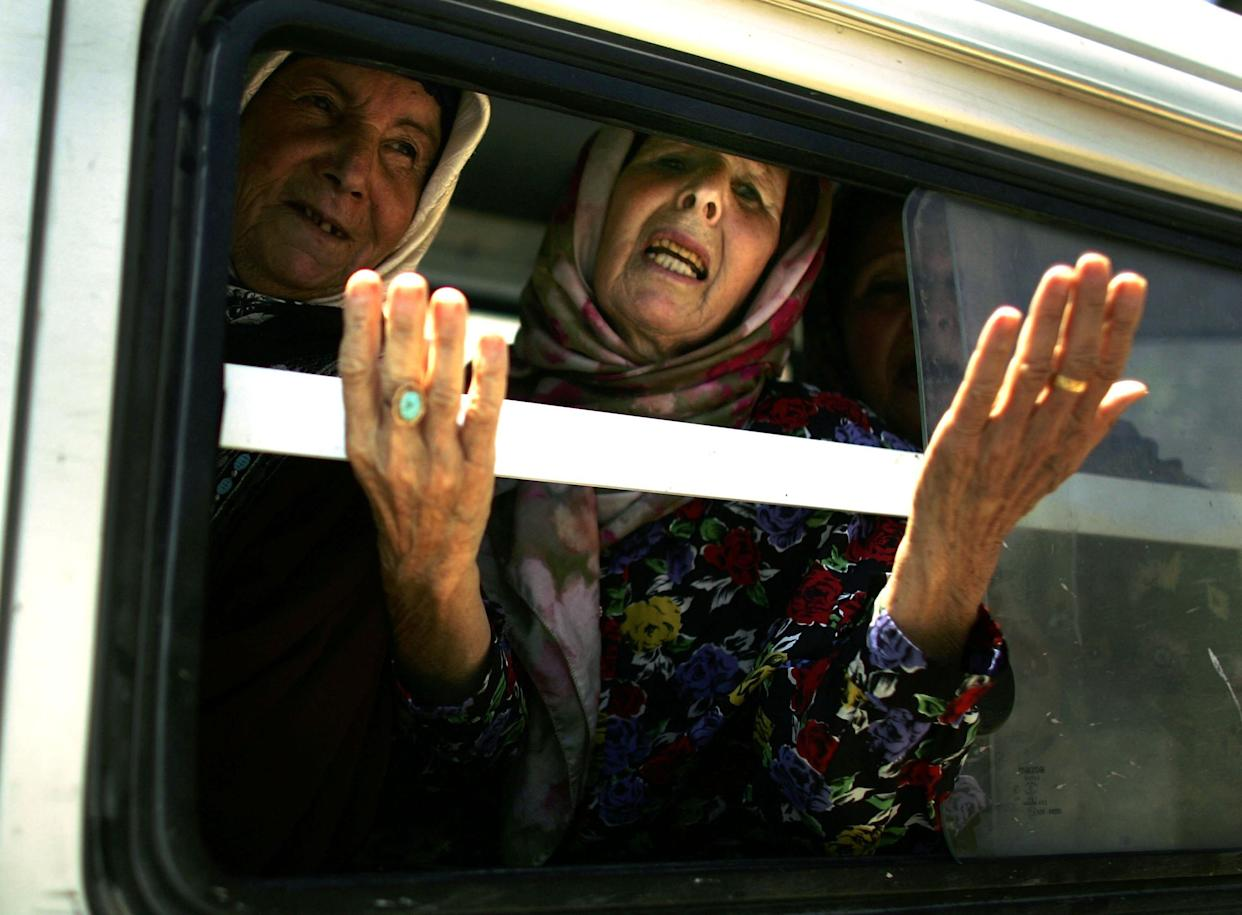 A woman gestures from a van carrying displaced people, one of thousands of civilians fleeing their southern villages as a forty eight hour halt of the Israeli bombing campaign allows access out of the area July 31, 2006 in Tyre, Lebanon.