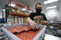 Bill Mathis packages THC products in Hazel Park, Mich., Thursday, April 29, 2021. A former teacher, Mathis has taken a new job in Michigan's newly legalized cannabis industry. The pay is better, the hours more regular, the stress less, he says. No longer does he worry that he'll catch COVID-19. (AP Photo/Paul Sancya)