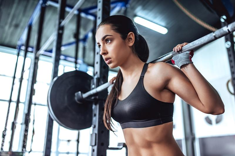 Attractive young sporty woman is working out in gym. gym training. Muscular woman is squatting with barbell