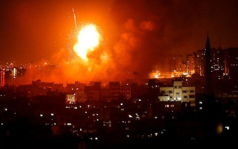 A fireball explodes during Israeli air strikes in Gaza City - Credit: AFP