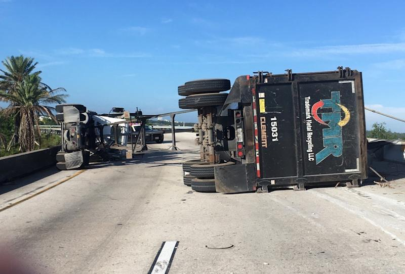 In this photo provided by the Florida Highway Patrol, a semitrailer hauling scrap metal is shown in Orange County, Florida, on Saturday, July 15, 2017.. The highway patrol said scrap metal fell from the truck onto a van after the truck lost control and overturned on an overpass. The van driver and the semi driver had only minor injuries. (Florida Highway Patrol via AP)