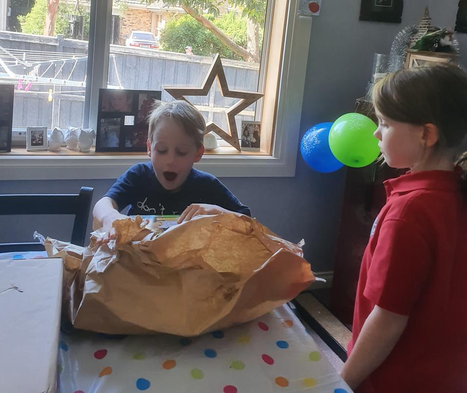 Nash Zabielski, pictured opening a present, was very excited to receive the note for his birthday and it is still hanging on the family's fridge.