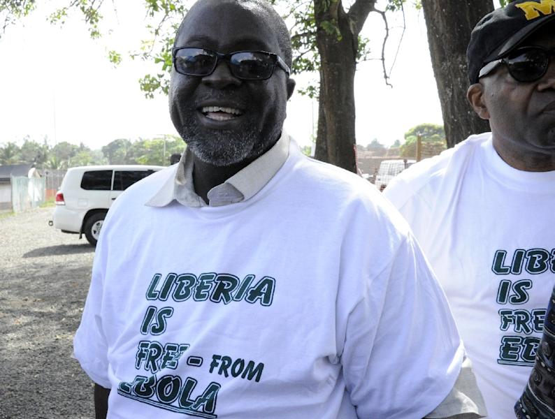 """Liberian Information Minister Lewis Brown (L) wears a t-shirt reading """"Liberia is free from Ebola"""" during the World Health Organization announcement of the end of Ebola in Liberia, on May 9, 2015 in Monrovia (AFP Photo/Zoom Dosso)"""