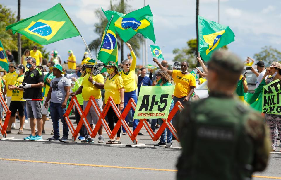 Supporters of Brazilian President Jair Bolsonaro demonstrate against quarantine and social distancing measures imposed by governors and mayors to combat the new coronavirus outbreak and demand military intervention (AI-5) in Brasilia on April 19, 2020. (Photo by Sergio LIMA / AFP) (Photo by SERGIO LIMA/AFP via Getty Images)