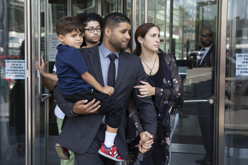 "Juan Rodriguez, holding his son Tristan, leaves Bronx Criminal Court with his wife Marissa after a hearing, Thursday, Aug. 1, 2019 in New York. The New York father has pleaded not guilty to manslaughter and other charges in the deaths of their 1-year-old twins left in a car on Friday while he put in a day at work. Prosecutors say Rodriguez told police he thought he had dropped the twins off at day care. They say he told police ""I blanked out. My babies are dead. I killed my babies."" (AP Photo/Mark Lennihan)"