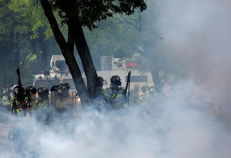 Riot police take position while clashing with opposition supporters during a rally against President Nicolas Maduro in Caracas