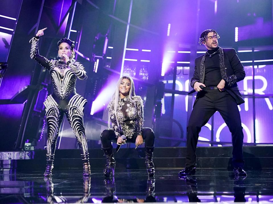 Ivy Queen, Nesi and Bad Bunny, in silver and black, perform on stage.