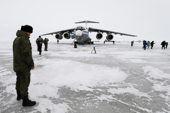 A Russian officer stands near a landed Il-76 military cargo plane on the Alexandra Land island near Nagurskoye, Russia, Monday, May 17, 2021. Once a desolate home mostly to polar bears, Russia's northernmost military outpost is bristling with missiles and radar and its extended runway can handle all types of aircraft, including nuclear-capable strategic bombers, projecting Moscow's power and influence across the Arctic amid intensifying international competition for the region's vast resources. (AP Photo/Alexander Zemlianichenko)