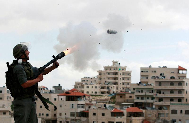 An Israeli border police officer fires tear gas towards Palestinian stone-throwers in East Jerusalem neighbourhood of Issawiya March 16, 2010. Dozens of Palestinian stone-throwers clashed with Israeli police in East Jerusalem on Tuesday on a
