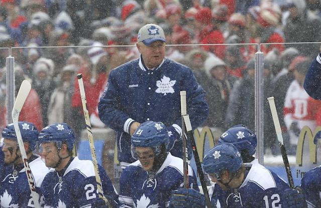 Toronto Maple Leafs head coach Randy Carlyle, cetner, talks to his team during the first period of the Winter Classic outdoor NHL hockey game against the Detroit Red Wings at Michigan Stadium in Ann Arbor, Mich., Wednesday, Jan. 1, 2014. (AP Photo/Paul Sancya)