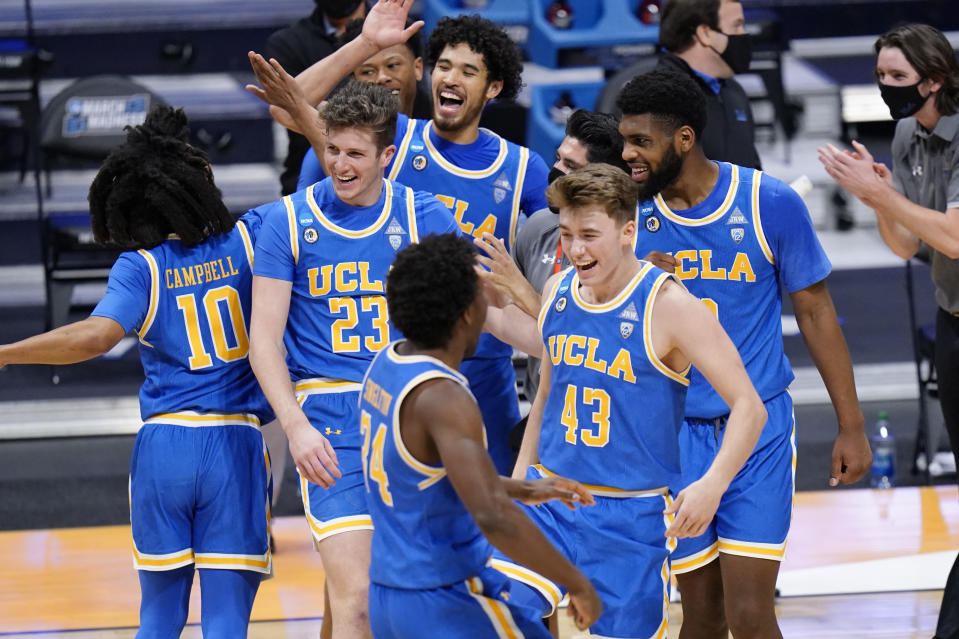 UCLA basketball players celebrate their win over BYU after a first-round game in the NCAA college basketball tournament at Hinkle Fieldhouse in Indianapolis, Saturday, March 20, 2021. (AP Photo/AJ Mast)