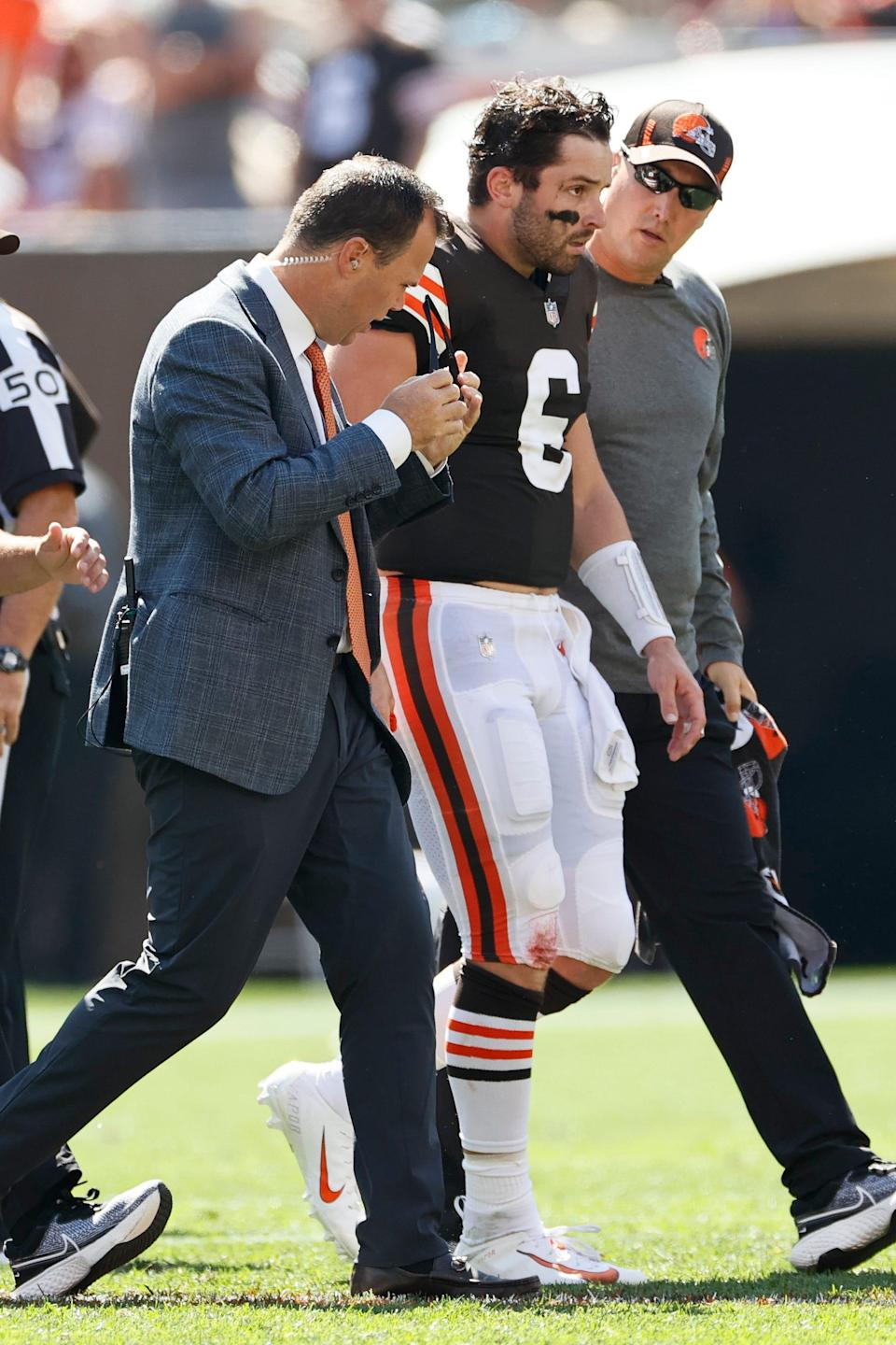 Cleveland Browns quarterback Baker Mayfield (6) is walked off the field after an injury during the first half of an NFL football game against the Houston Texans, Sunday, Sept. 19, 2021, in Cleveland. (AP Photo/Ron Schwane)