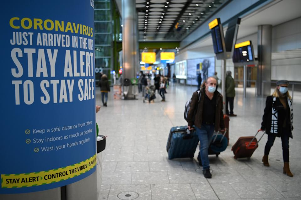 Coronavirus health warnings are seen in the arrivals hall after at London Heathrow Airport in west London, on January 15, 2021. - International travellers will need to present proof of a negative coronavirus test result in order to be allowed into England, or face a £500 ($685, 564 euros) fine on arrival, from January 18. (Photo by DANIEL LEAL-OLIVAS / AFP) (Photo by DANIEL LEAL-OLIVAS/AFP via Getty Images)