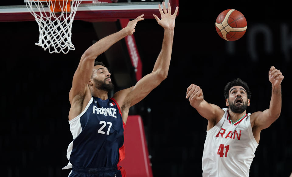 France's Rudy Gobert (27), left, and Iran's Arsalan Kazemi (41) fight for a rebound during men's basketball preliminary round game at the 2020 Summer Olympics, Saturday, July 31, 2021, in Saitama, Japan. (AP Photo/Charlie Neibergall)