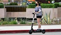 A commuter on electric scooter wears her facemask in Los Angeles on June 29, 2020, where bars and beaches are shutting back down