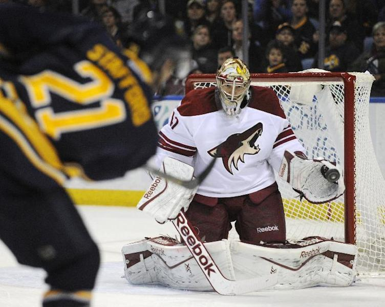 Buffalo Sabres right winger Drew Stafford (21) shoots the puck at Phoenix Coyotes goaltender Mike Smith (41) during the first period of an NHL hockey game in Buffalo, N.Y., Monday, Dec. 23, 2013. (AP Photo/Gary Wiepert)