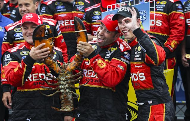 Brad Keselowski, right, gestures while celebrating with members of his team, holding a lobster, in Victory Lane after winning the NASCAR Sprint Cup series auto race at New Hampshire Motor Speedway on Sunday, July 13, 2014, in Loudon, N.H. (AP Photo/Cheryl Senter)