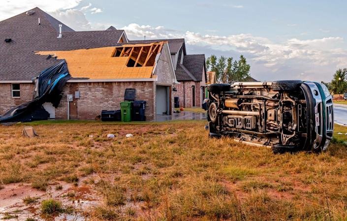 Storm damage to a home and an overturned truck caused by a tornado that hit in the early morning hours near SW 49th St. and Czech Hall Rd. in Mustang, Okla. on Wednesday, Oct. 13, 2021.
