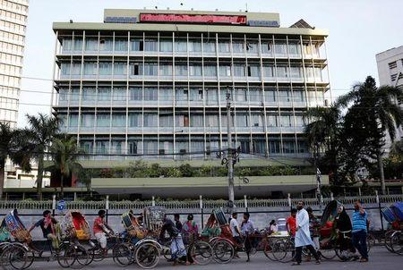 Commuters walk in front of the Bangladesh central bank building in Dhaka