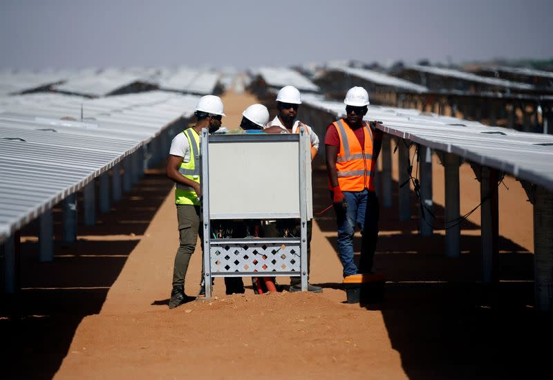 Workers set up the photovoltaic solar panels at the Benban plant in Aswan