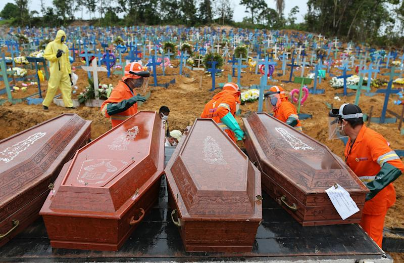 Coffins are unloaded to be buried in a mass grave at the Nossa Senhora cemetery in Manaus, Amazon state, Brazil on May 6, 2020. (Photo by MICHAEL DANTAS / AFP) (Photo by MICHAEL DANTAS/AFP via Getty Images)