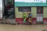 "Residents walk along a house on a flooded street heading to a shelter ahead of the expected landfall of cyclone Amphan, in Dacope of Khulna district on May 20, 2020. - Several million people were taking shelter and praying for the best on Wednesday as the Bay of Bengal's fiercest cyclone in decades roared towards Bangladesh and eastern India, with forecasts of a potentially devastating and deadly storm surge. Authorities have scrambled to evacuate low lying areas in the path of Amphan, which is only the second ""super cyclone"" to form in the northeastern Indian Ocean since records began. (Photo by Munir uz Zaman / AFP) (Photo by MUNIR UZ ZAMAN/AFP via Getty Images)"