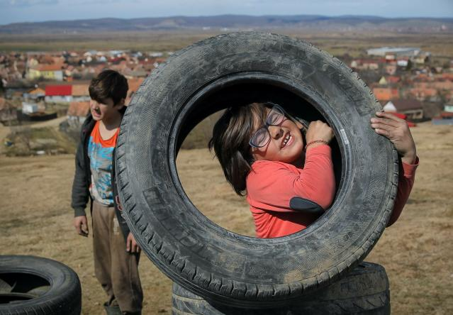 In this photo taken on Sunday, March 10, 2019, a little girl struggles to lift a tire during a ritual marking the upcoming Clean Monday, the beginning of the Great Lent, 40 days ahead of Orthodox Easter, on the hills surrounding the village of Poplaca, in central Romania's Transylvania region. Romanian villagers burn piles of used tires then spin them in the Transylvanian hills in a ritual they believe will ward off evil spirits as they begin a period of 40 days of abstention, when Orthodox Christians cut out meat, fish, eggs, and dairy. (AP Photo/Vadim Ghirda)