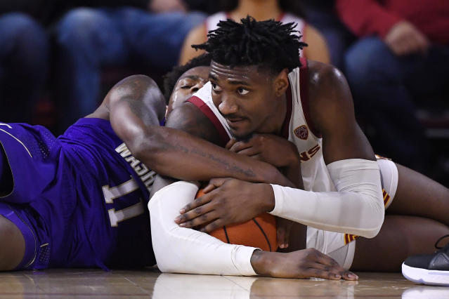 Washington guard Nahziah Carter, left, and Southern California guard Jonah Mathews tie up the ball during the first half of an NCAA college basketball game Thursday, Feb. 13, 2020, in Los Angeles. (AP Photo/Mark J. Terrill)
