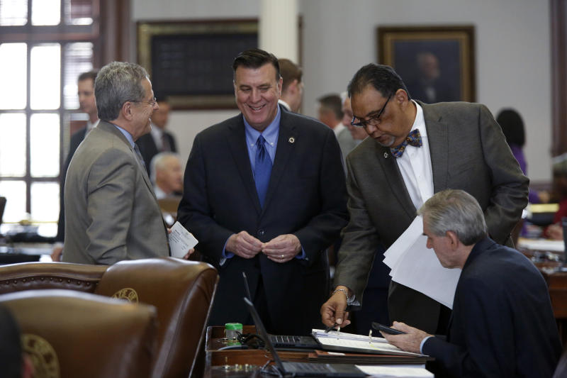 FILE - In this April 11, 2019 file photo Rep. Rick Miller, R-Sugar Land, talks with Rep. Paul Dennis, R-Houston, Joe Deshotel, D-Beaumont, and Rep. Ed Thompson, R-Pearland in the Texas House of Representatives chamber in Austin, Texas. Drowned out by the coronavirus and national politics, Republican and Democratic operatives are nonetheless quietly preparing for a battle of state legislative supremacy later this year that could have a profound effect on political power for the next decade to come. This week, national Republicans are rolling out their first offensive target list for the November state legislative elections. It's focused on 115 Democratic-held seats in a dozen states where Republicans hope to strengthen their power or dent that of Democrats. (James Gregg/Austin American-Statesman via AP)