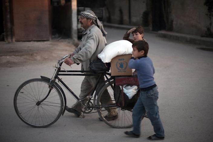 A Syrian man and his children carry sacks of aid provided by the World Food Programme in Kafr Batna, in the rebel-held Eastern Ghouta area on March 1, 2016 (AFP Photo/Amer Almohibany)