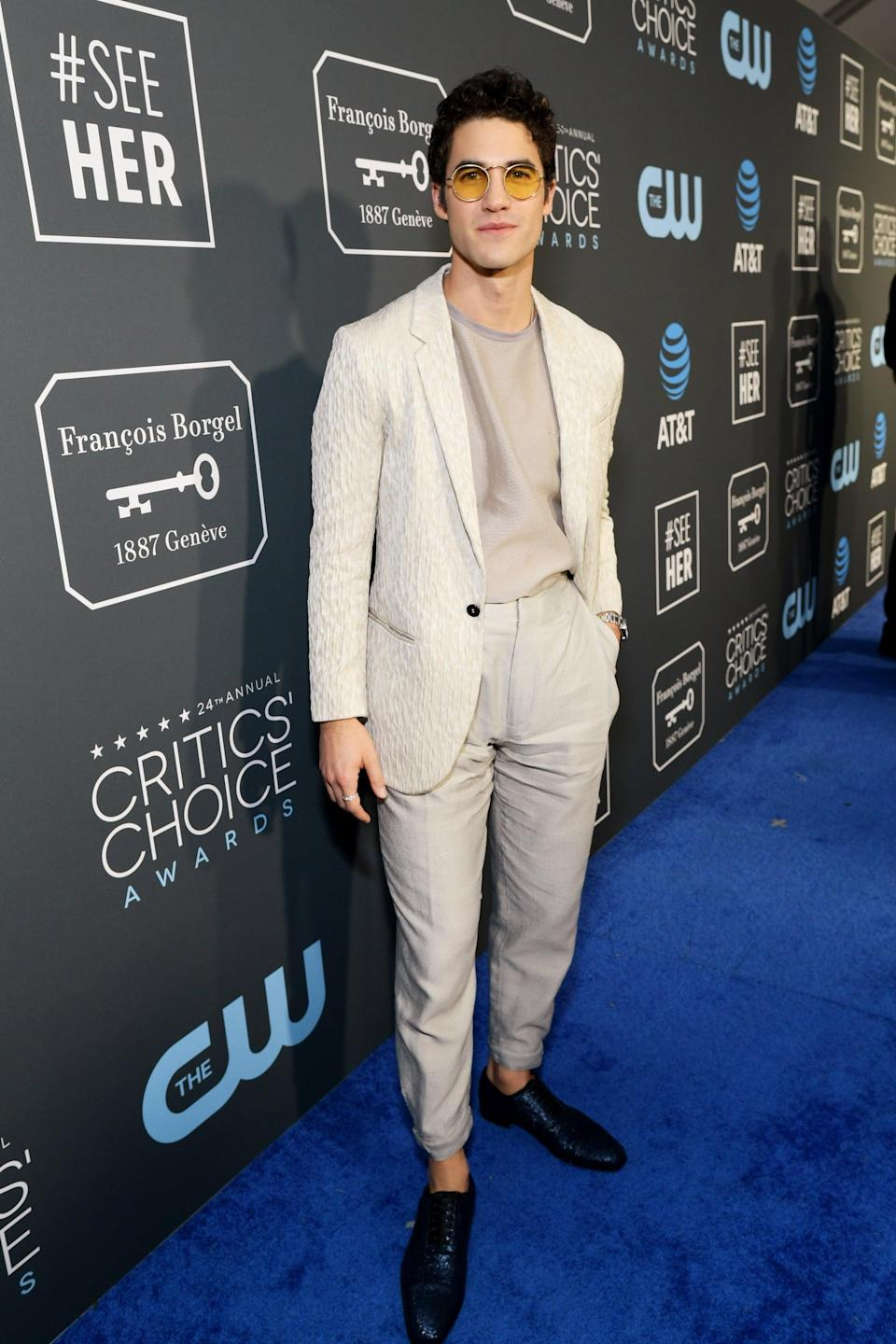 <p>Darren Criss wearing a cropped suit with Oliver Peoples sunglasses and a John Hardy ring.</p>
