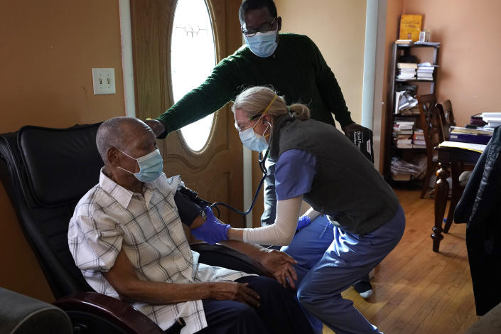 Edouard Joseph, 91, left, has his blood pressure taken by geriatrician Megan Young, right, as Joseph's son, Edouard F. Joseph, top, offers support after his father received a COVID-19 vaccination, Thursday, Feb. 11, 2021, at his home in the Mattapan neighborhood of Boston. Millions of U.S. residents will need COVID-19 vaccines brought to them because they rarely or never leave home. Doctors and nurses who specialize in home care are leading this push and starting to get help from state and local governments around the country. (AP Photo/Steven Senne)