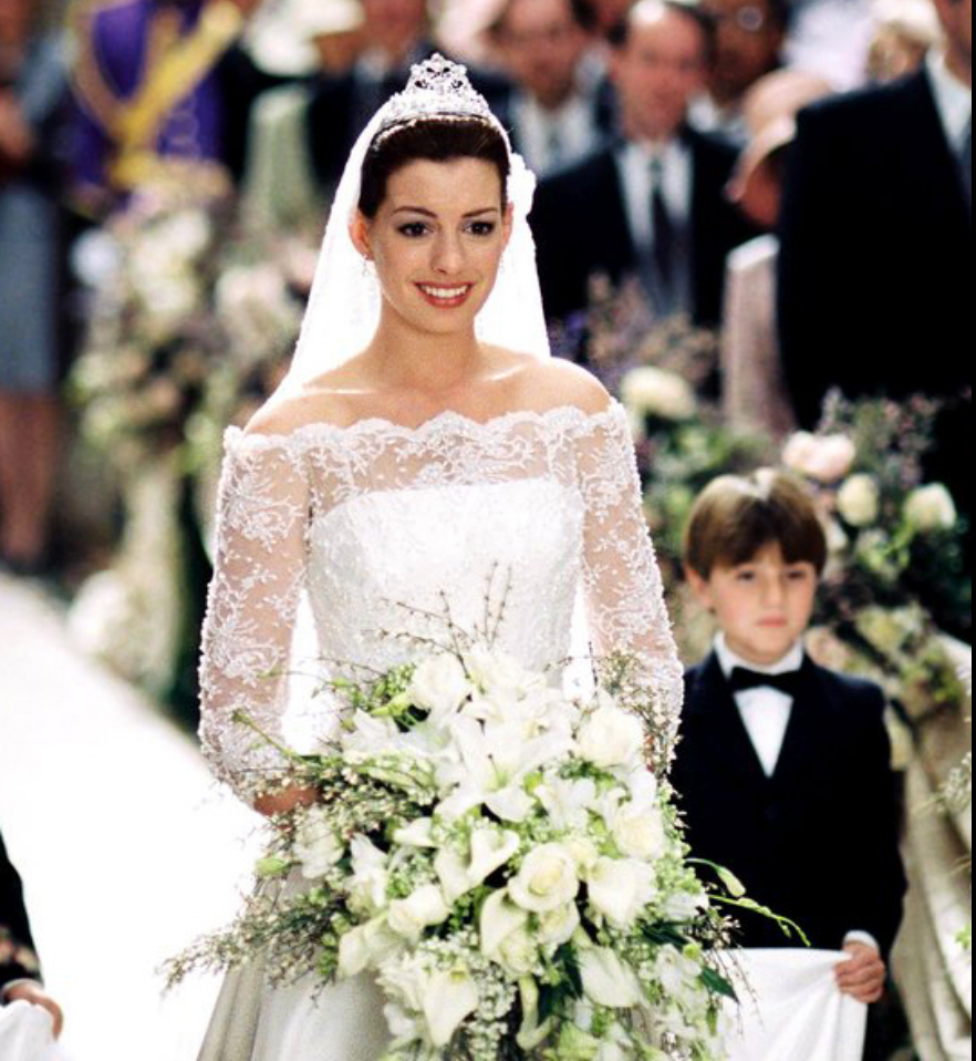 """<p>Even though Mia Thermopolis decided to ascend to the throne *without* taking a husband (YGG), we're glad she eventually said """"I do"""" so that we were able to see her lace off-the-shoulder gown that was fit for a princess. </p>"""