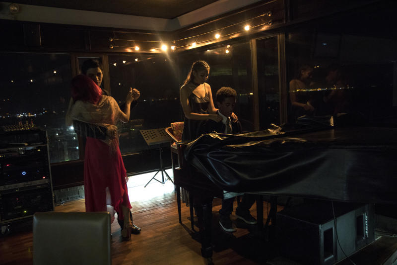 A man plays the piano as a couple dances in El Girasol restaurant in Maracaibo, Venezuela, May 22, 2019. Amid shortages of cash, food, water, medicine, power and gasoline, there are signs of people carrying on, finding a way forward. (AP Photo/Rodrigo Abd)