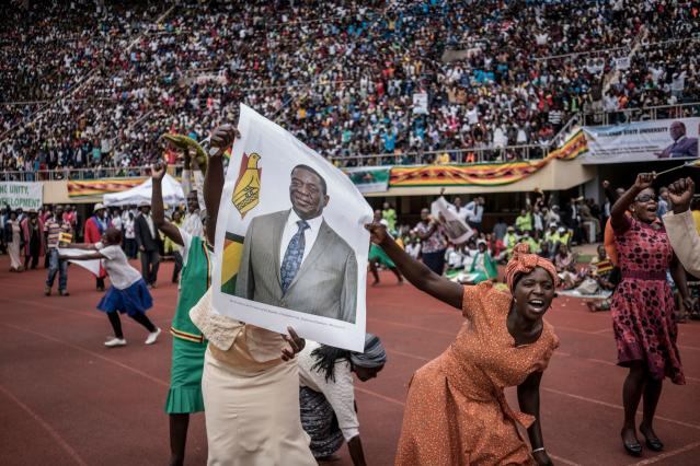 "<p>TOPSHOT – Supporters hold poster of the newly sworn-in President Emmerson Mnangagwa during the Inauguration ceremony at the National Sport Stadium in Harare, on November 24, 2017.<br> Zimbabwe's newly sworn-in President Emmerson Mnangagwa vowed during his inauguration speech on November 24 to protect foreign investments in the country as he sought to lay out his economic credentials. ""In this global world no nation is, can, or need be an island. All foreign investments will be safe in Zimbabwe,"" he told a crowd of tens of thousands at his inauguration ceremony. (Photo: Marco Longari/AFP/Getty Images) </p>"