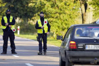 """Polish police officers stop cars going in and out of an area along the border with Belarus where a state of emergency is in place, in Krynki, Poland, on Wednesday, Sept. 29, 2021. After enduring a decade of war in Syria, Boshra al-Moallem and her two sisters seized their chance to flee, but the journey proved terrifying and nearly deadly. Al-Moallem, originally from Homs but who displaced to Damascus by the war, is one of thousands of people who have traveled to Belarus in recent weeks and then found herself helped to cross the border with the help of Belarusian guards, something the EU considers a form of """"hybrid war"""" waged against the bloc with the use of human lives. (AP Photo/Czarek Sokolowski)"""