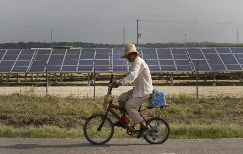 **CORRECTS SPELLING OF CANTARRANA** In this July 18, 2013 photo, a farmer rides past a row of solar panels in Cantarana, Cuba. The country's first solar farm opened this spring with little fanfare and no prior announcement. It boasts 14,000 photovoltaic panels which in a stroke more than doubled the country's capacity to harvest energy from the sun. (AP Photo/Franklin Reyes)
