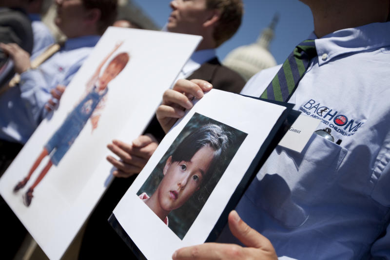 In this May 5, 2010 file photo, fathers that lost their children to spousal abduction to Japan hold photos of their children during a news conference on Capitol Hill in Washington.  Japan's parliament has approved joining an international child custody treaty amid foreign concerns that Japanese mothers can take children away from foreign fathers without recourse. The upper house of parliament on Wednesday, May 22, 2013,  voted to join the 1980 Hague Convention on international child abduction following passage by the more powerful lower house last month.(AP Photo/Evan Vucci, File)