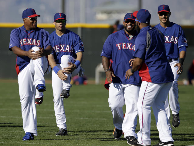 Texas Rangers' Adrian Beltre, left, Seattle Seahawks quarterback Russell Wilson, second from left, Rangers' Prince Fielder, center rear, Elvis Andrus, right front and Alex Rios, right rear, stretch before a morning work out during spring training baseball practice, Monday, March 3, 2014, in Surprise, Ariz. (AP Photo/Tony Gutierrez)