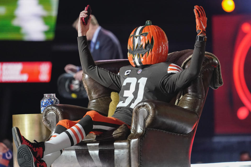 A chosen Cleveland Browns fan wearing a uniform and a pumpkin mask on his head sits on stage and cheers as the team was making its selection in the NFL football draft, Thursday, April 29, 2021, in Cleveland. (AP Photo/Tony Dejak)