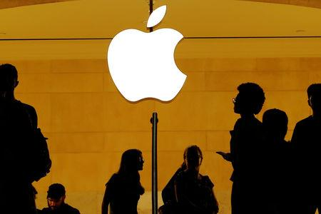 FILE PHOTO: Customers walk past an Apple logo inside of an Apple store at Grand Central Station in New York