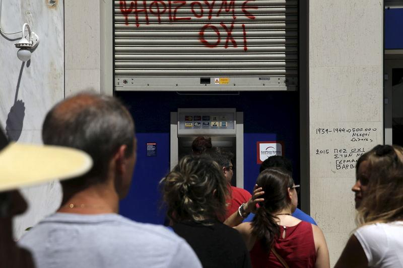 People line up at an ATM outside a Eurobank branch in Athens