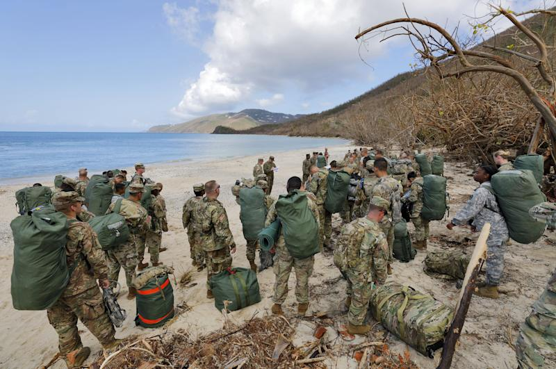 Army soldiers from the 602nd Area Support Medical Company gather on a beach as they await transport on a Navy landing craft while evacuating in advance of Hurricane Maria, in Charlotte Amalie, St. Thomas, U.S. Virgin Islands, Sept.17, 2017. (Jonathan Drake / Reuters)